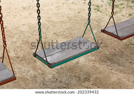 Wooden swing chair in park - stock photo