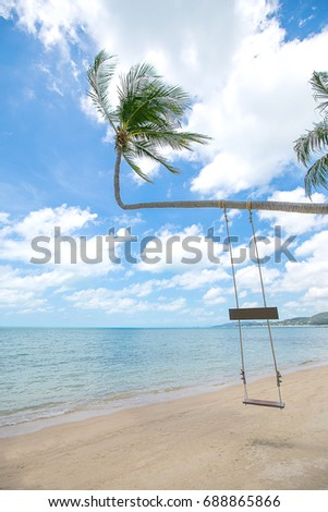 Wooden swing hang from coconut tree over tropical beach, white sand, blue sky background.