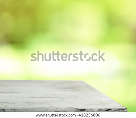 Wooden table against green background - stock photo