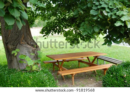 wooden table and bench in garden - stock photo