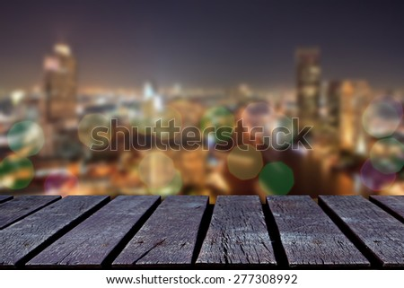 Wooden table and blurred city. - stock photo