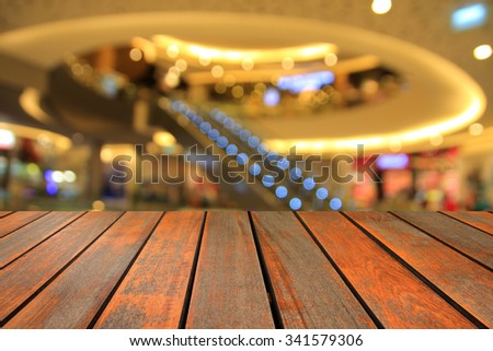 Wooden table and blurred photo of department store shopping mall center and people background - stock photo