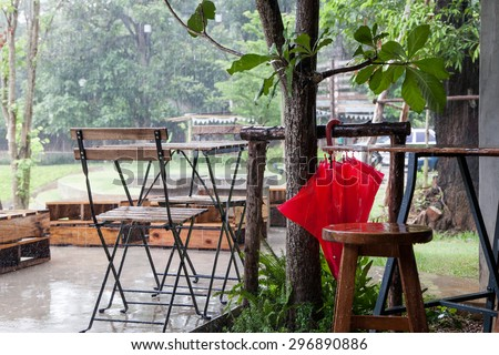 Wooden table and chair with umbrella in garden in rainy day
