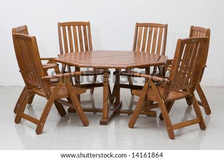 Wooden table and chairs on a tiled floor - stock photo