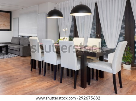 Wooden table and white chairs in dining room - stock photo