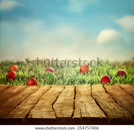 Wooden table. Easter design with Easter hunt and tabletop Space for your montage - stock photo