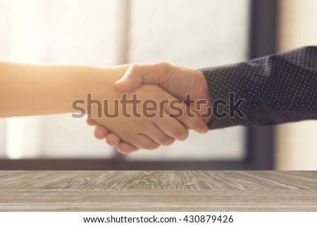 wooden table for display or montage your product with blur background of businessman handshaking for business acquisition concept