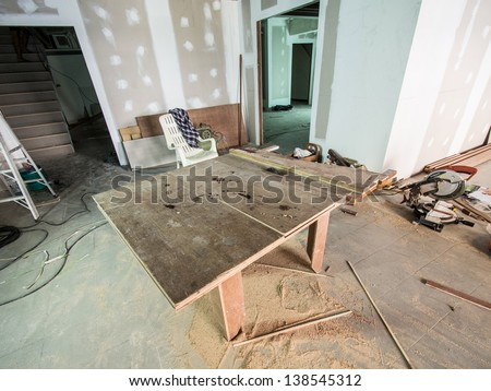 wooden table for labor working on renovation work with unfinished wall painting and other equipments - stock photo