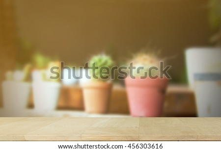 Wooden table for presentation product with Soft focus of Succulents or cactus in pot. - stock photo
