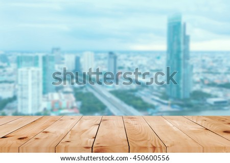 Wooden table in front of  blurred city landscape