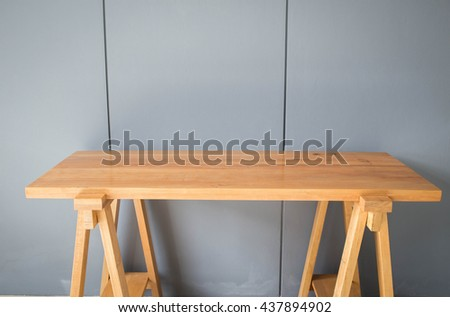 Wooden table in front of the gray background.