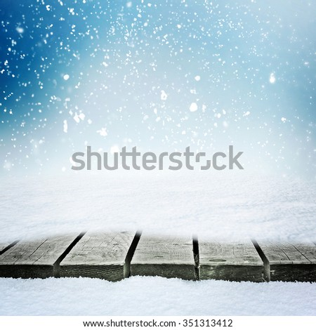 Wooden table in snowdrift and falling snow over winter sky - stock photo