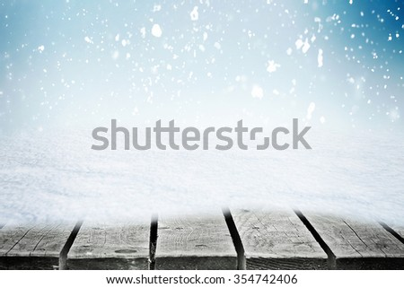 Wooden table in snowdrift over snowing sky - stock photo