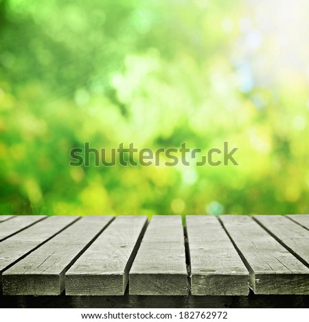 Wooden table in summer meadow for picnic - stock photo