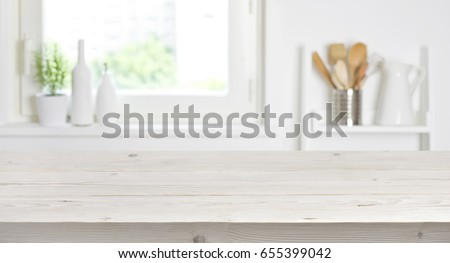 Wooden table on blurred background of kitchen window and shelves