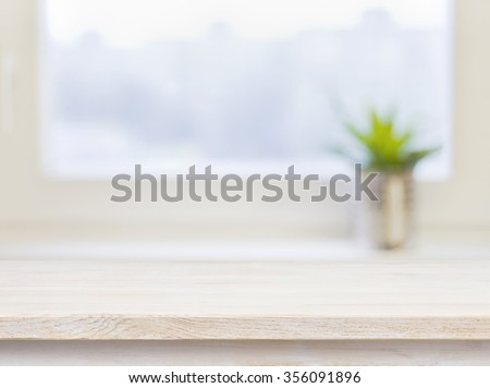 Wooden table on defocuced winter window background - stock photo