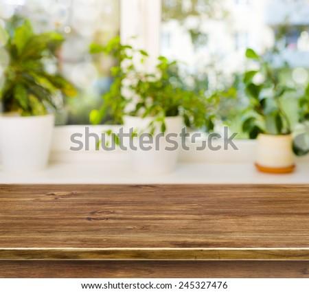 Wooden table on defocused windowsill background - stock photo