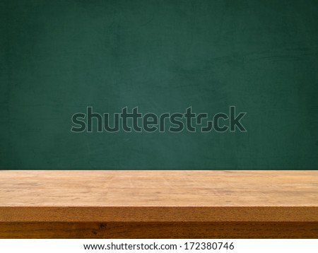 Wooden table on green chalkboard - stock photo