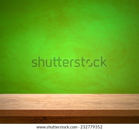 Wooden table on green wall background - stock photo