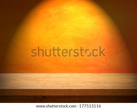 Wooden table on orange wall with light - stock photo
