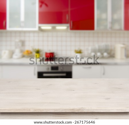 Wooden table on red modern kitchen bench interior background - stock photo