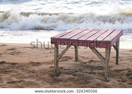 Wooden table on the beach, selective focus, vintage processed. - stock photo