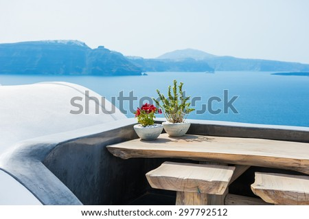 Wooden table on the terrace with sea view. Santorini island, Greece. Selective focus - stock photo