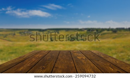 Wooden table outdoors with beautiful summer field background - stock photo