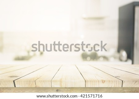 Wooden table over blured kitchen interior background