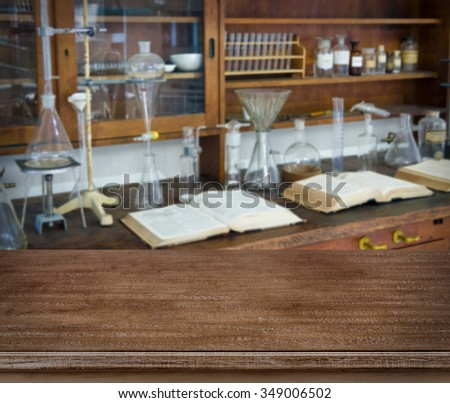 Wooden table over defocused vintage chemical laboratory background - stock photo