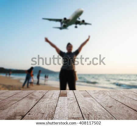 Wooden table top on blurred some people relax on the beach sunset in twilight with plane come in the land, Can be used for display or montage your products - stock photo