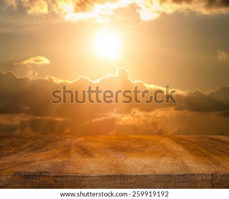 Wooden table top on sunset sky - stock photo