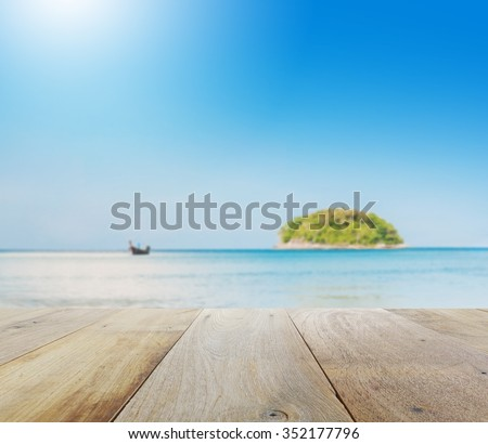 wooden table top with blur of beautiful seascape with blue sea beach island and the long tail boat under clear sky in summer,kata beach - phuket - stock photo