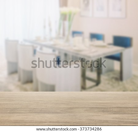 wooden table top with blur of dining table and comfortable chairs with elegant table setting - stock photo