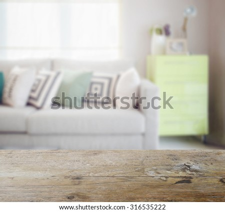 wooden table top with blur of geometric pattern pillows on cozy sofa and green sideboard in living room - stock photo