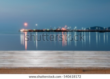 Wooden table top with blurred sea sunset background,retro filter effect
