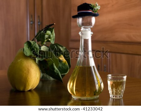 Wooden table with a bottle of brandy and ripe yellow quince on it. - stock photo