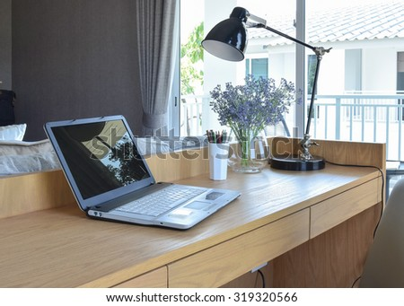 wooden table with computer notebook,pencil,lamp and artificial flowers in modern working area at home - stock photo