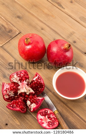 Wooden table with cut pomegranate and bowl of fresh juice