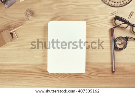 Wooden table with nottepad pens and office stuff in vintage style - stock photo
