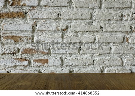 Wooden table with rustic white brick wall - stock photo