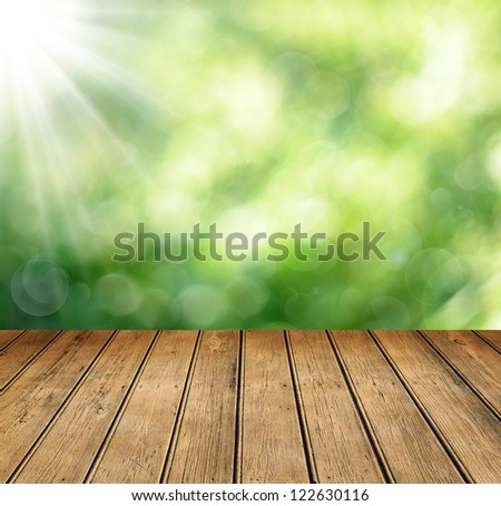 wooden table with space for your photo montage and green color of background - stock photo