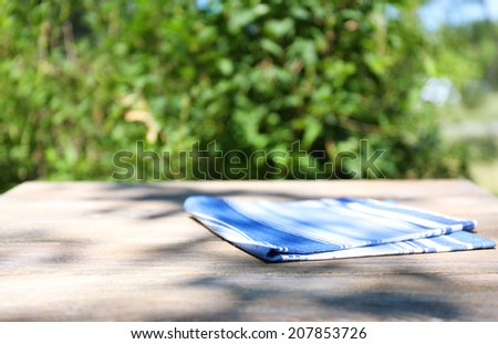 Wooden table with tablecloth, outdoors