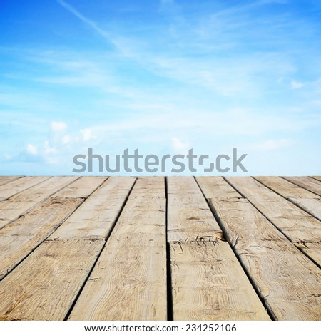 Wooden table with view to sky - stock photo