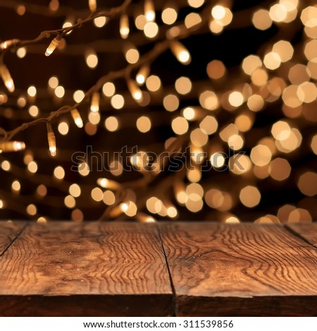 wooden table with yellow holiday lights on background - stock photo