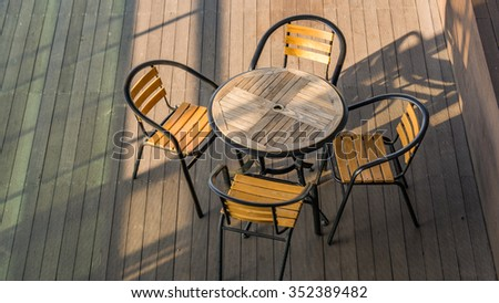 Wooden tables and chairs in the cafe and the morning sun. - stock photo
