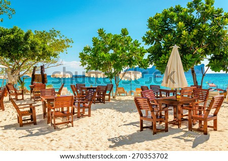 Wooden tables with sun umbrellas at a luxury resort close to an exotic beach - stock photo