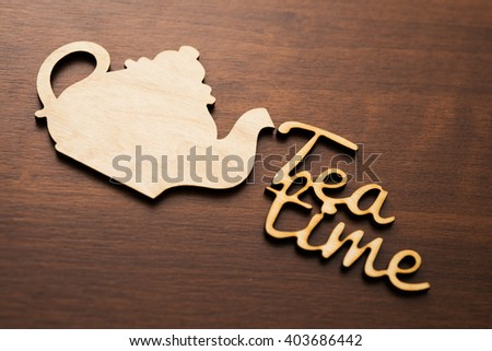 wooden teapot sign and tea time words lie on table from natural material.  - stock photo