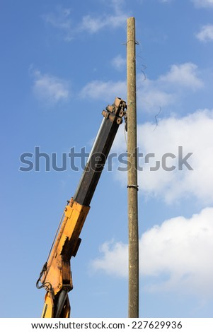 Wooden telephone pole hangs vertically in the air from a yellow crane. Crane hook lifting the wooden telephone pole out. - stock photo