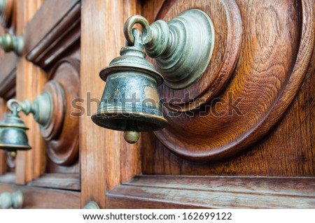 wooden temple door with bells in Hindu temple close up (Sri Srinivasa Perumal) - stock photo